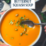 Overhead shot of a spoon in a bowl of vegan butternut squash soup with text title overlay
