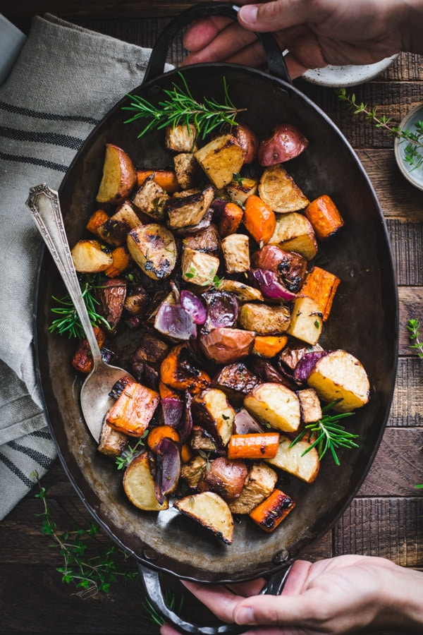 Overhead image of hands holding a pan of balsamic roasted root vegetables on a wooden table