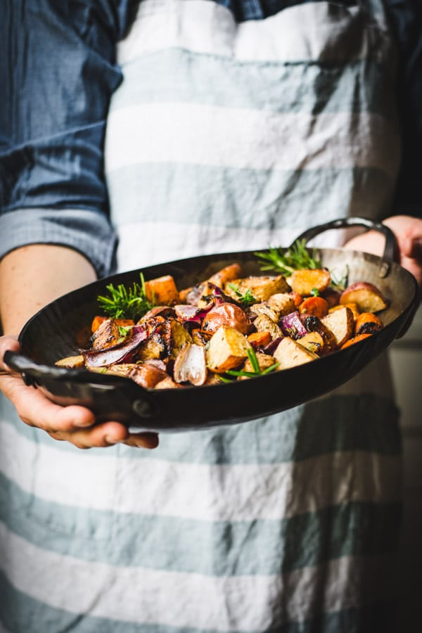 Hands holding pan roasted root vegetables