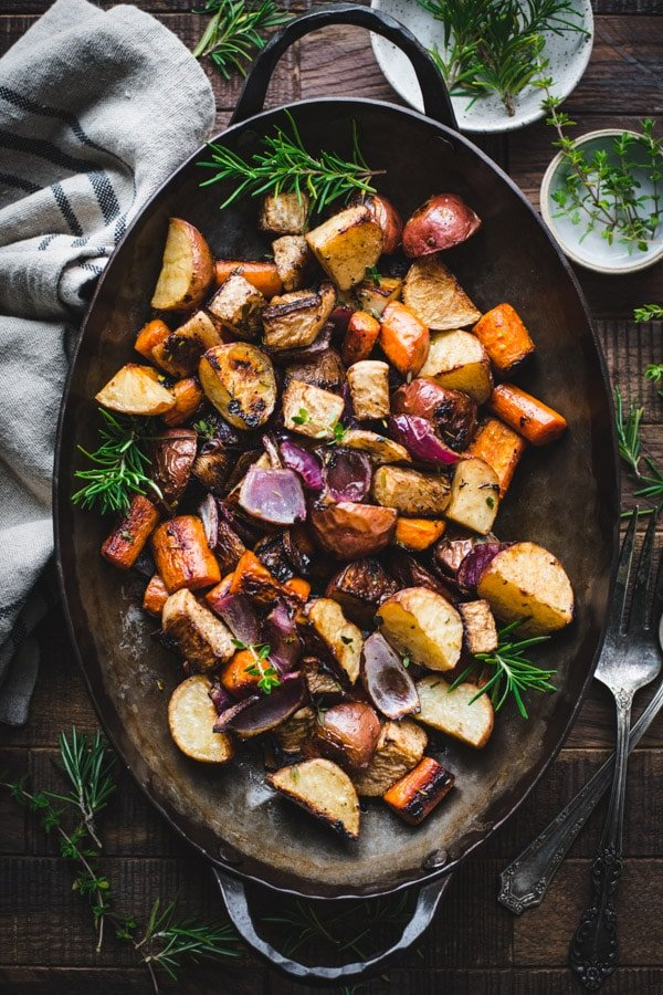 Overhead image of a cast iron roasting pan full of roasted root vegetables with rosemary.