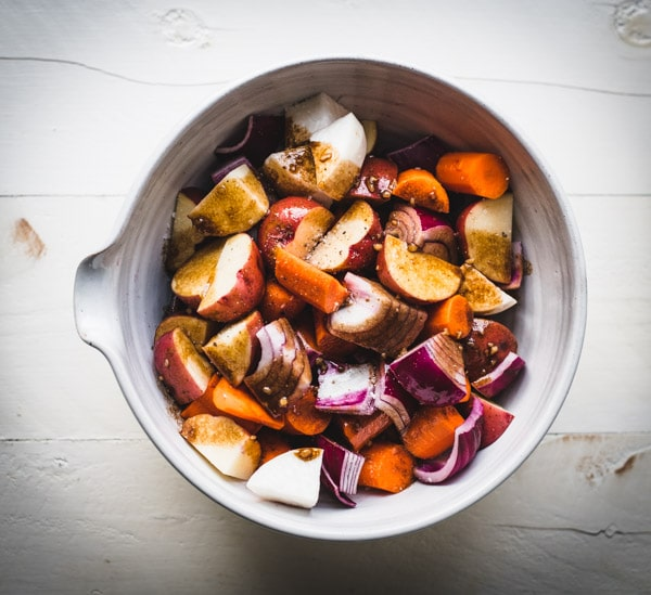 Balsamic on a bowl of carrots potatoes onion and turnips