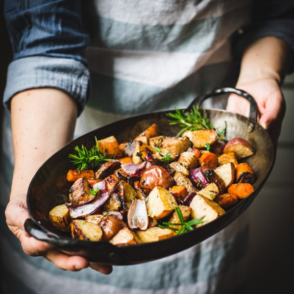 Square shot of hands holding a pan of roasted root vegetables