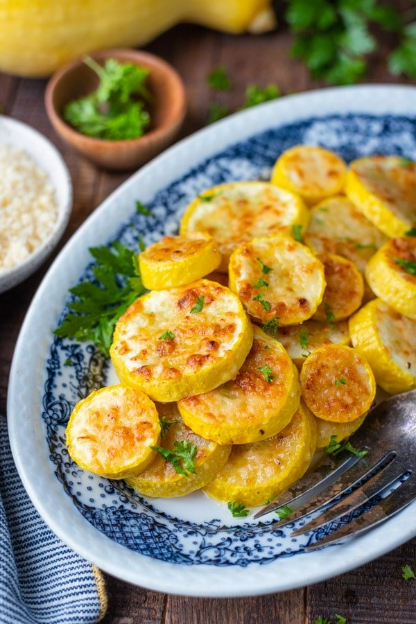 Side shot of a plate of oven roasted yellow squash with parmesan and herbs on top
