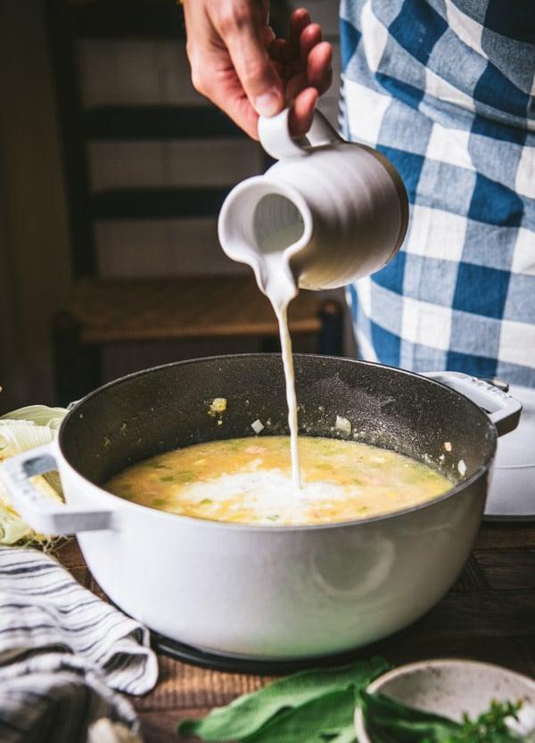 Pouring cream into a pot of shrimp soup