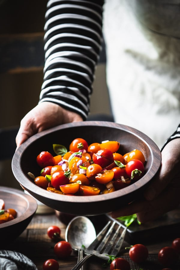 Hands holding a bowl of fresh tomato salad with basil and balsamic