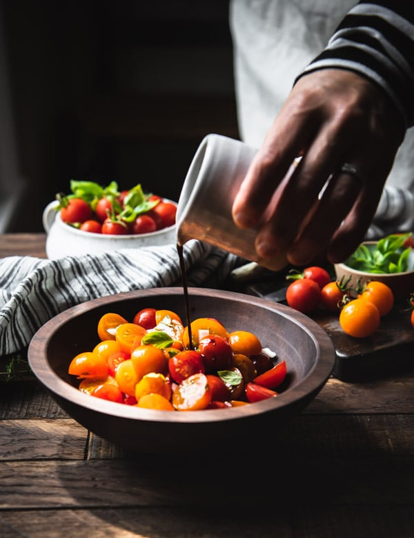 Pouring balsamic dressing over a bowl of tomato salad