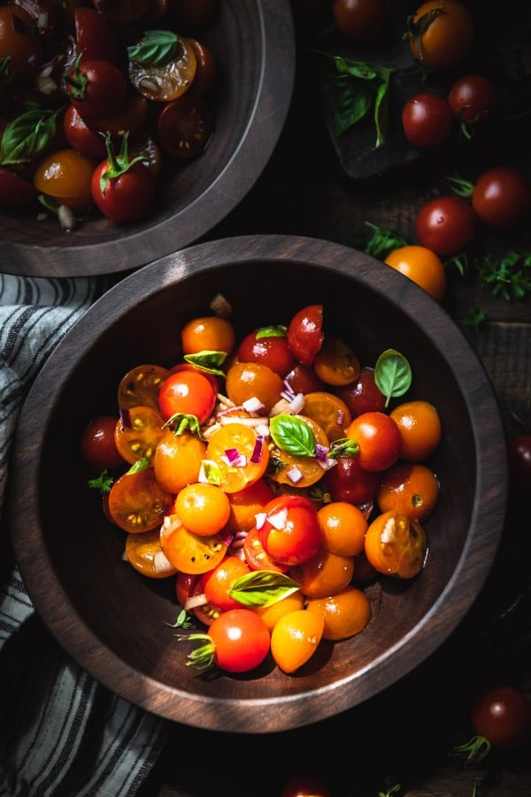 Close overhead shot of cherry tomato salad in a wooden bowl