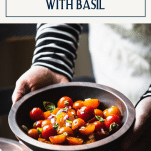 Side shot of hands holding a wooden bowl of tomato basil salad with text title box at top