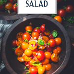 Overhead shot of a wooden bowl full of the best tomato salad recipe with text title overlay