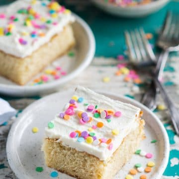 Slice of the best vanilla cake recipe on a white plate with sprinkles