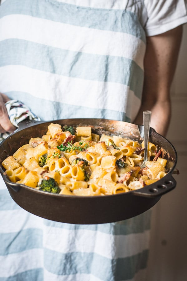 Hands holding a pasta bake in a skillet