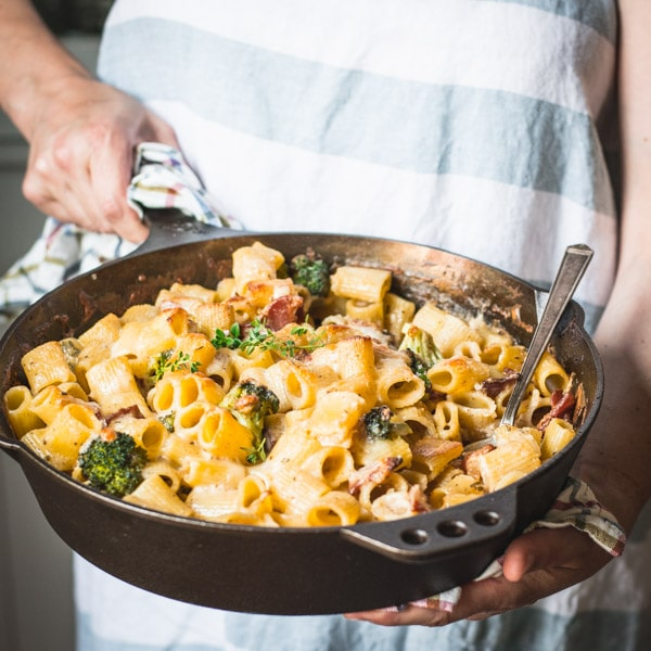 Square shot of hands serving a pan of cheesy pasta bake