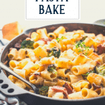 Close up side shot of cheesy rigatoni pasta bake with text title overlay