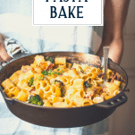 Hands holding a skillet of cheesy pasta bake with text title overlay