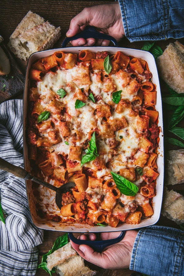 Overhead shot of two hands holding a pan of easy baked rigatoni with sausage