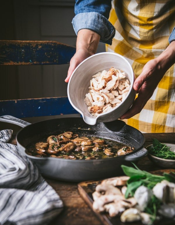 Adding chicken to a skillet with sauteed mushrooms