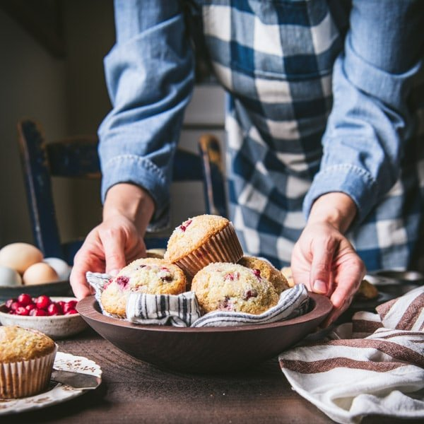Hands holding a basket of homemade fresh cranberry muffins.