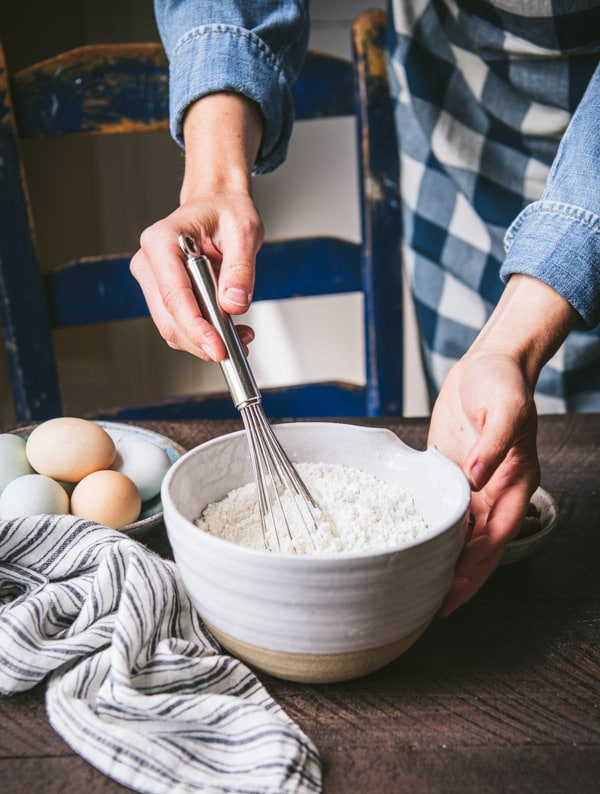 Whisking flour and dry ingredients in a white bowl