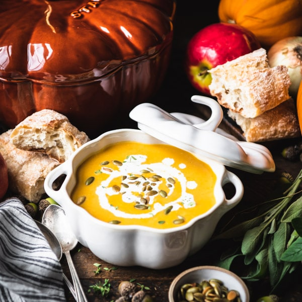 Square shot of a bowl of creamy pumpkin soup on a table surrounded by apples, onions, bread and pumpkins