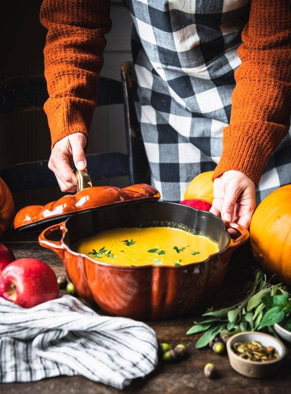 Hands serving a pumpkin shaped pot of creamy pumpkin soup on a table