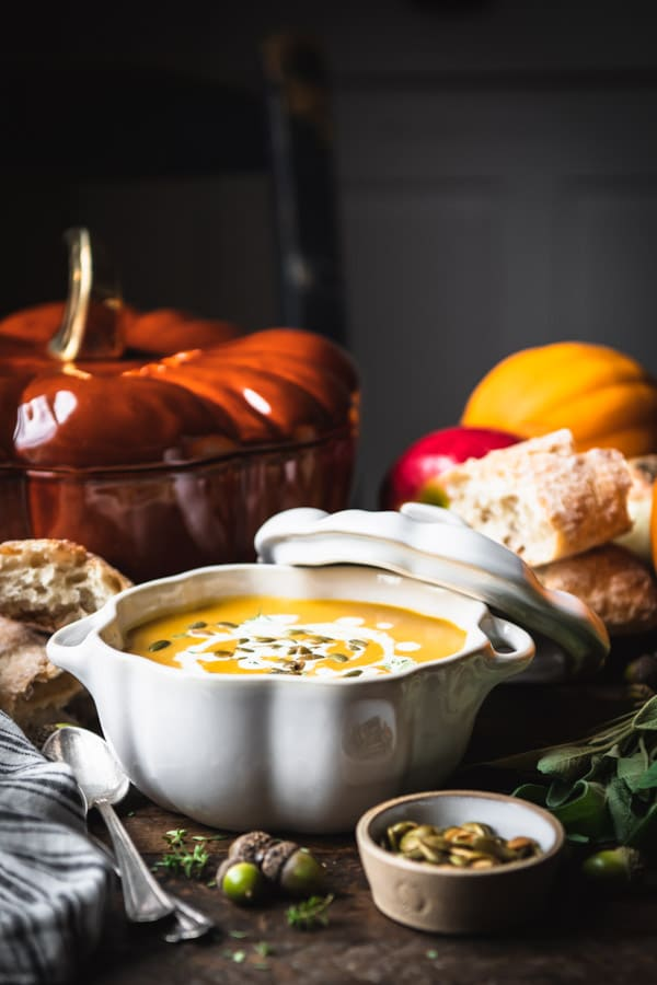 Side shot of a bowl of canned pumpkin soup with pumpkin shaped pot in the background