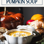 Side shot of pumpkin soup on a table with text title box at top