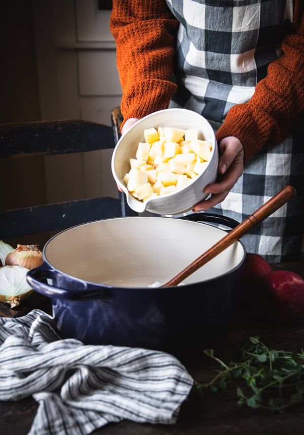 Adding diced apples to a pot of soup