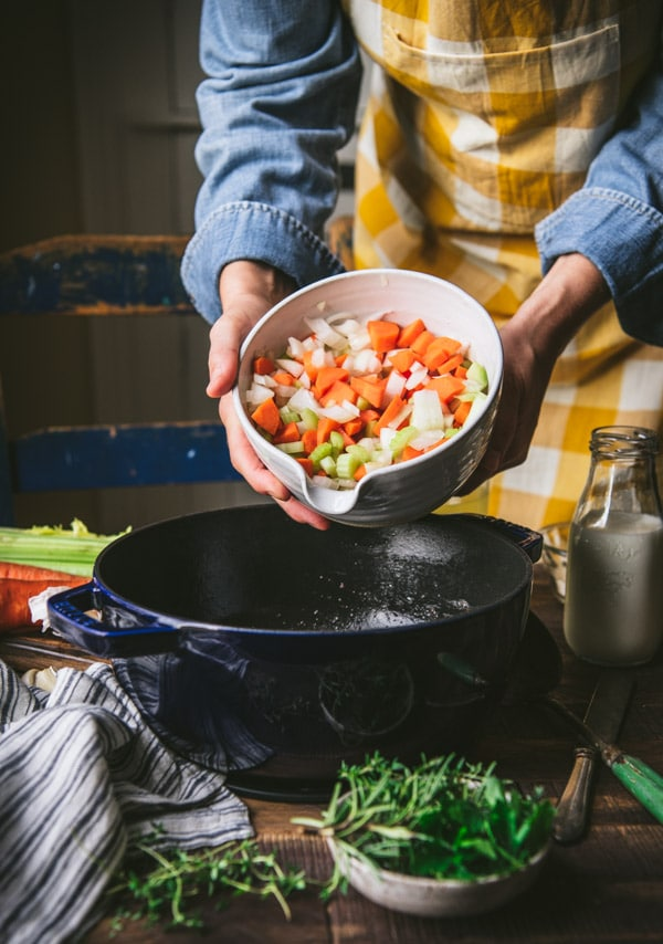 Adding vegetables to a Dutch oven for a soup recipe