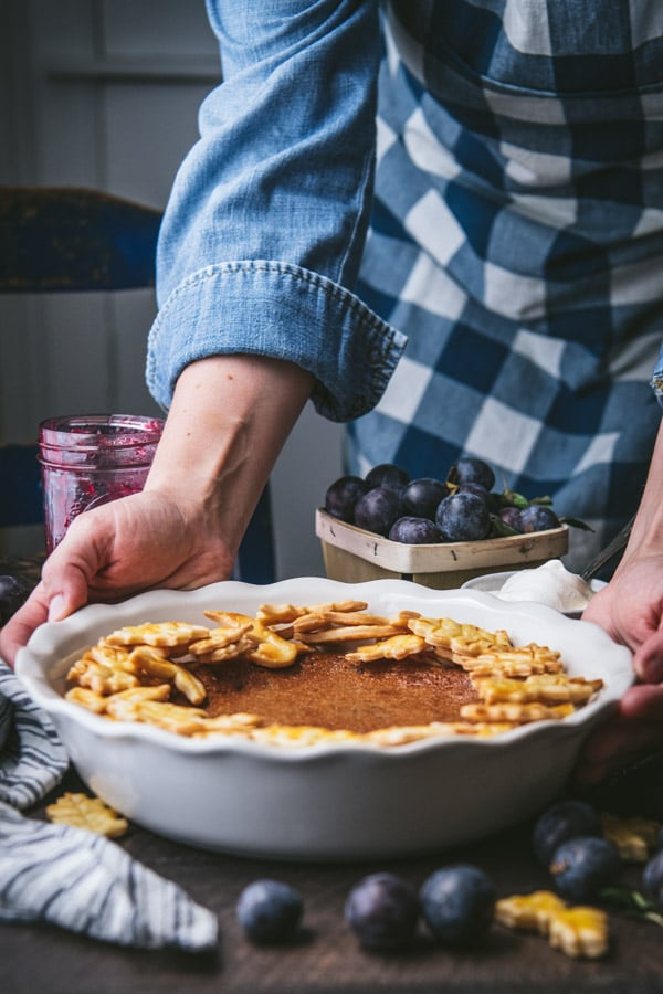 Hands holding a damson plum pie in a white dish.