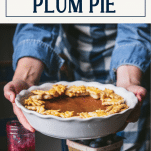 Hands holding a damson plum pie with text title box at top