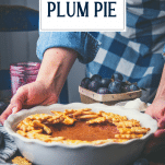 Hands serving a damson plum pie in a white dish with text title overlay