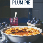 Side shot of damson plum pie on a table with text title overlay