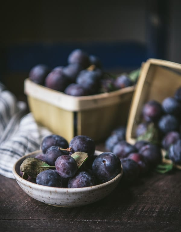 Fresh damson plums on a farmhouse table