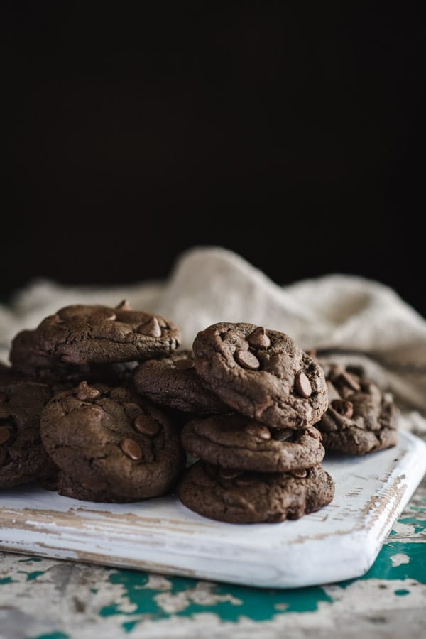 Side shot of easy double chocolate chip cookies served on a white wooden board
