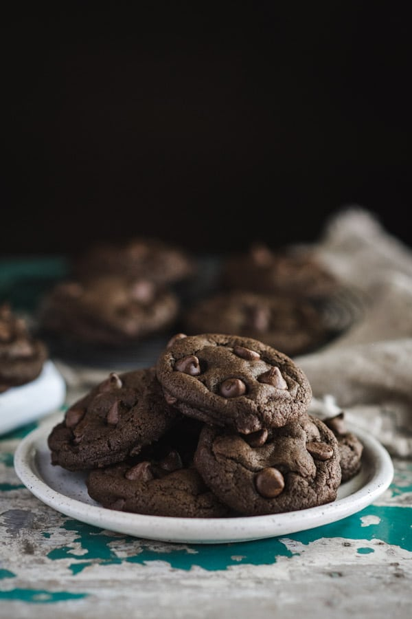 Side shot of a plate of soft and chewy double chocolate chip cookies