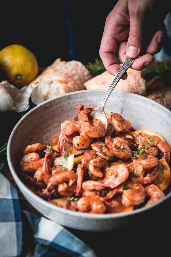 Spoon serving garlic and butter shrimp from a white bowl.