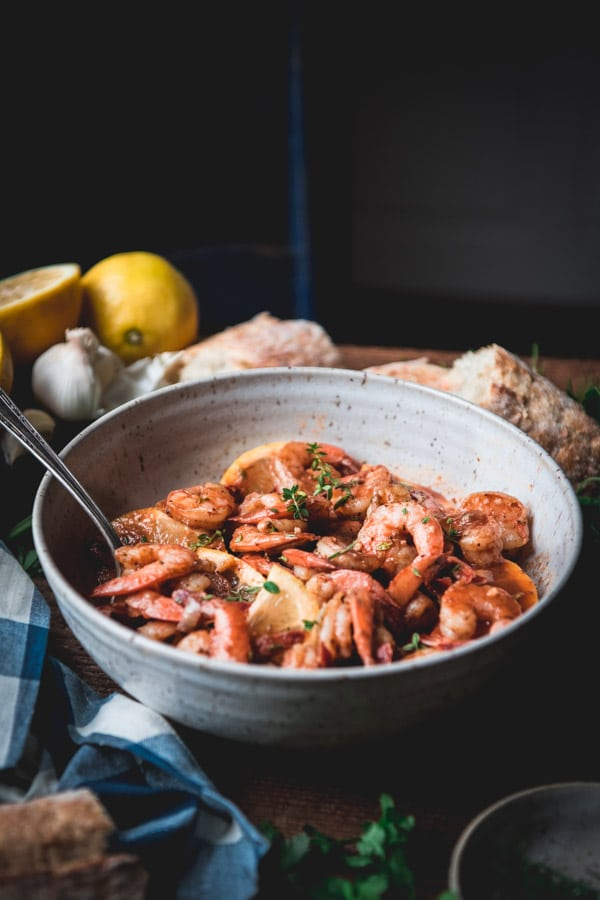 Bowl full of garlic and butter shrimp on a wooden farmhouse table.