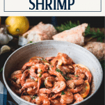 Side shot of a bowl of garlic butter shrimp with text title box at top.