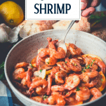 Side shot of a bowl of garlic butter shrimp with text title overlay
