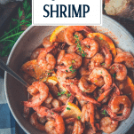 Close overhead shot of a bowl of garlic butter shrimp with text title overlay