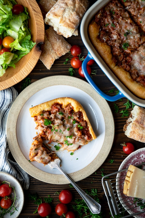 Overhead shot of Italian sausage crescent roll casserole on a plate with a fork