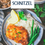 Overhead shot of a plate of pork schnitzel with text title overlay
