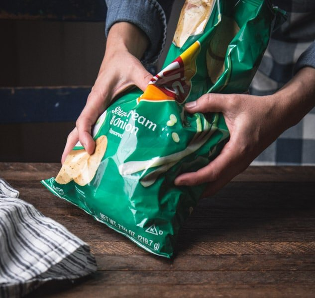 Crushing a bag of potato chips into fine crumbs