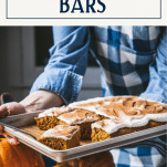 Tray of pumpkin bars with cream cheese frosting and text title box at top.