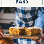 Side shot of pumpkin bars on a wooden cutting board with text title box at top.