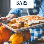 Hands holding a pan of pumpkin bars with cream cheese frosting and text title overlay.