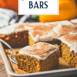 Side shot of a pan of pumpkin bars with cream cheese frosting and text title overlay.