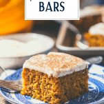 Slice of pumpkin bars on a plate with text title overlay.