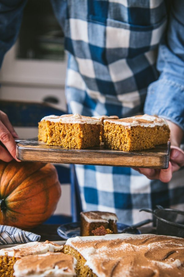 Hands holding easy pumpkin bars on a wooden cutting board.