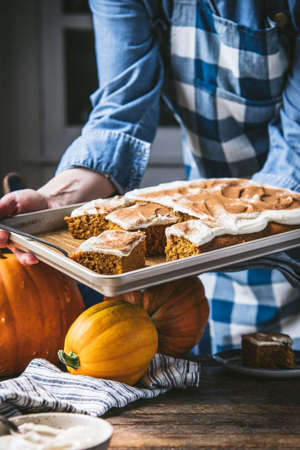 Hands holding a sheet pan of pumpkin bars with cream cheese frosting.